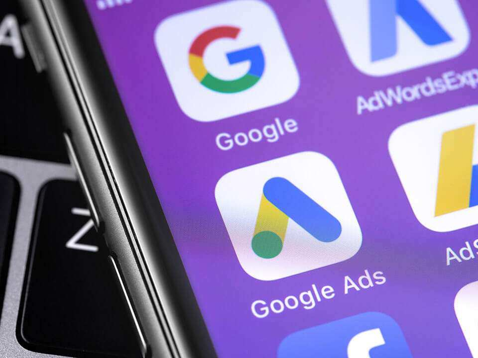 Google Ads AdWords app icon on smartphone screen and laptop can make the SEO process easier.